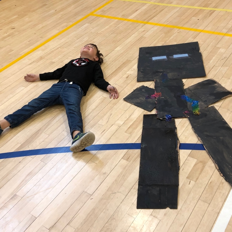 kid laying on floor next to an art version of self