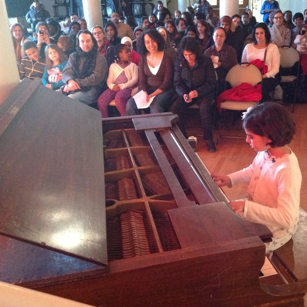 student plays piano for a crowd in the PS130 auditorium